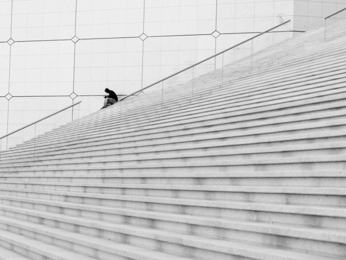 person sitting on staris of la defence in Paris