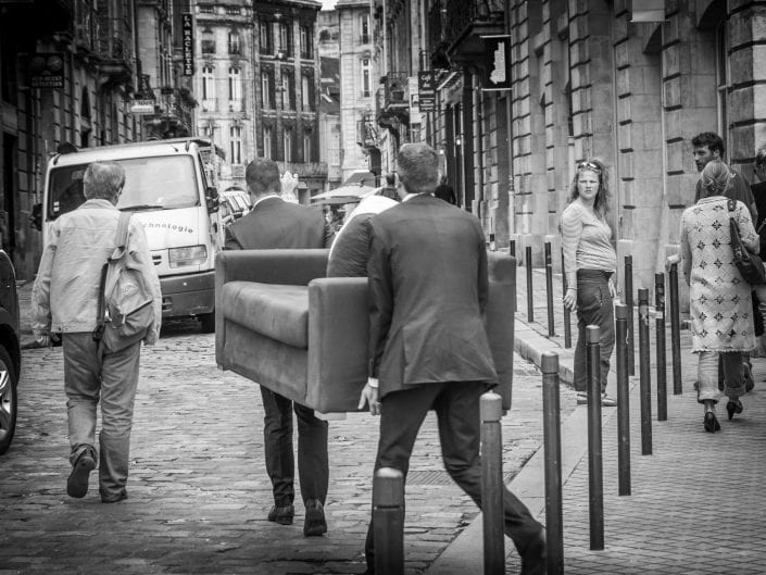 street photography black and white, men in suits moving a couch