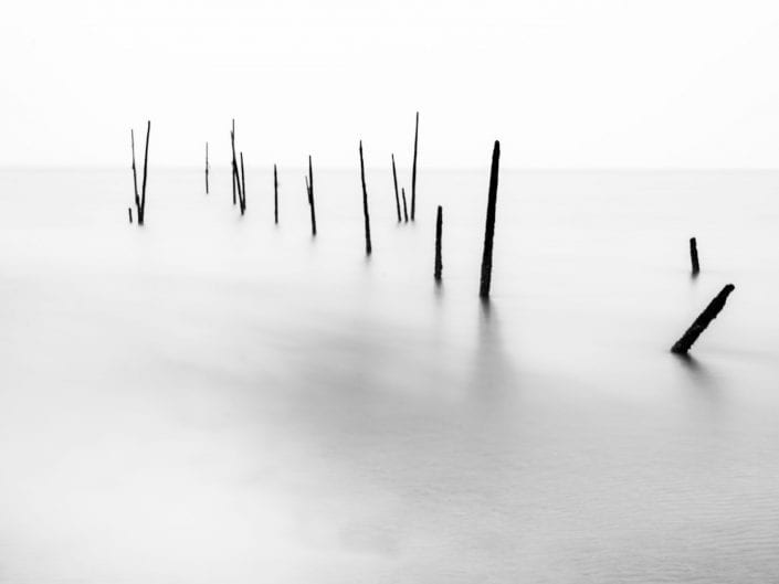 minimalist photo of poles in waterscape in Rockanje Netherlands, laong exposure, black and white