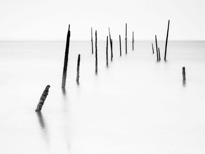minimalist photo of poles in waterscape in Rockanje Netherlands, long exposure, black and white