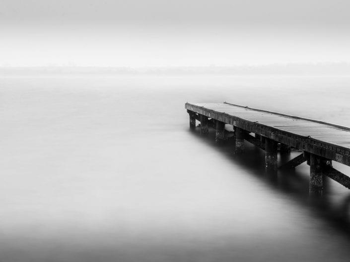 jetty , minimalist photo waterscape Vrouwenpolder Netherlands, black and white, long exposure