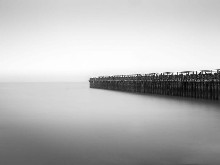black and white minimalist photo of jetty, waterscape Westkapelle Netherlands_