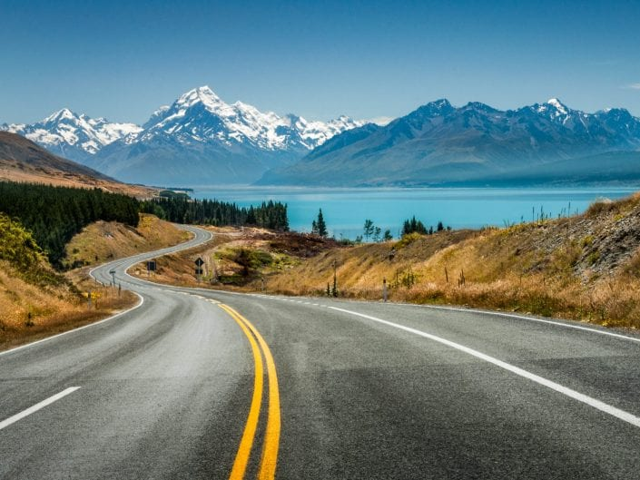 photo of gentle landscape of s-shaped road in New Zealand, lake Pukaki, view on mount Cook, yellow lines