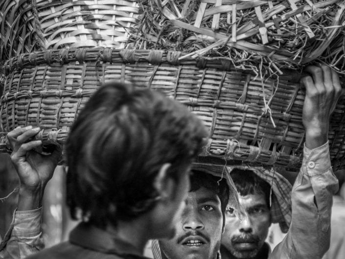 black and white street photography man carrying basket with fruits and vegetables on head in Mumbay India, wholesale market