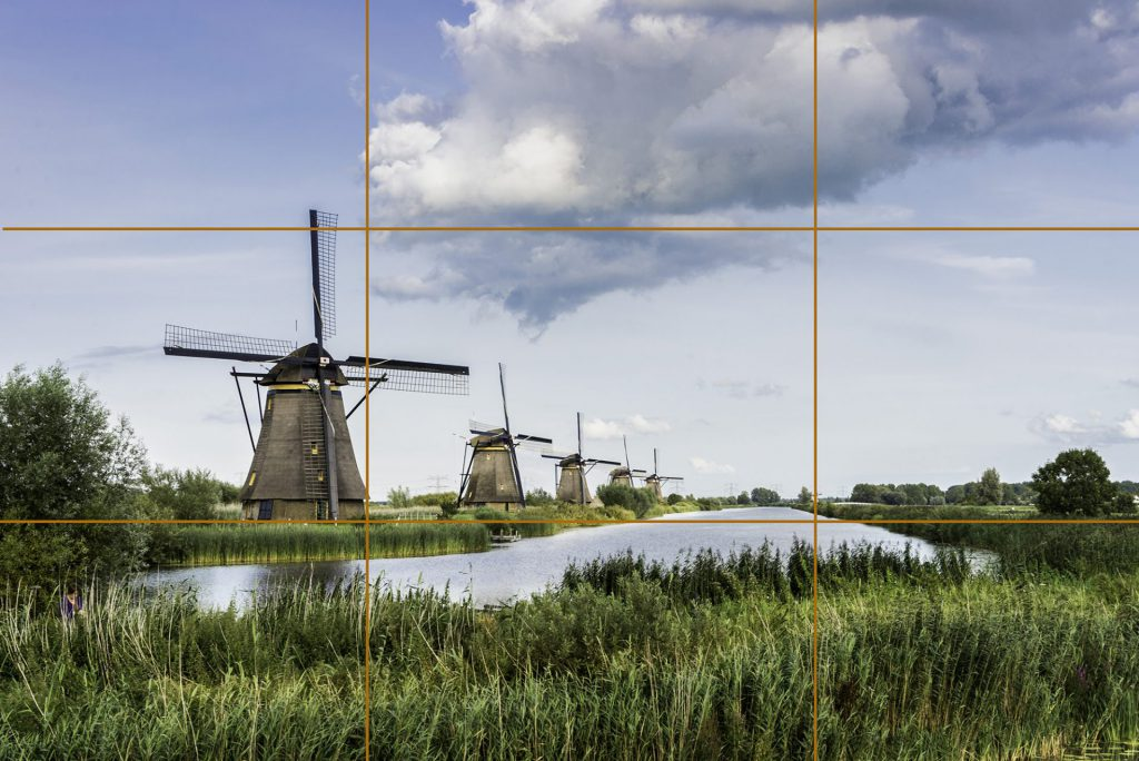 Landscape photo of row of windmills in Kinderdijk, the Netherlands with the horizon at 1/3
