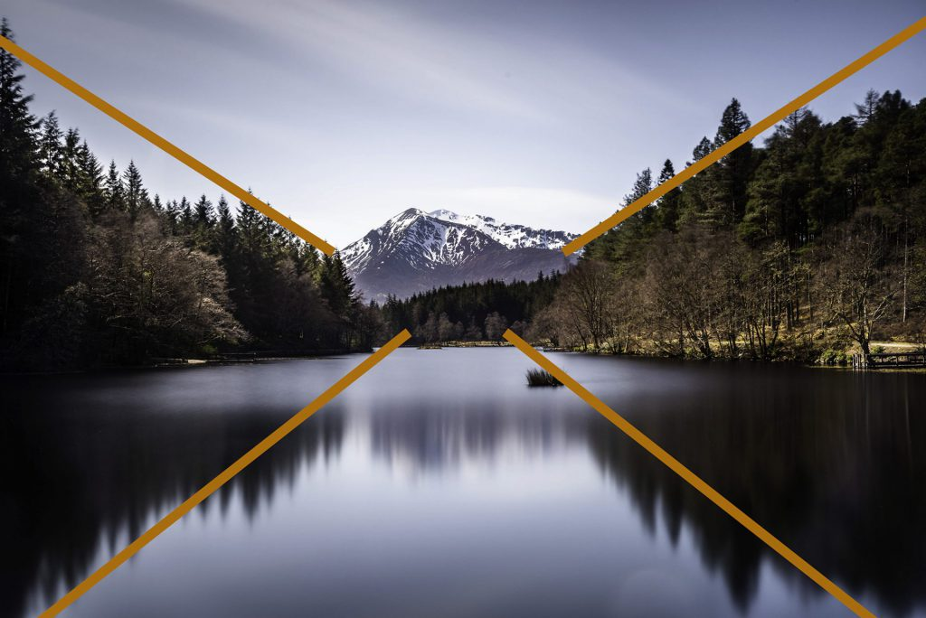 landscape photo with leading lines of trees and the reflection towards snowclad mountain at Loch Achtriochtan in Scotland