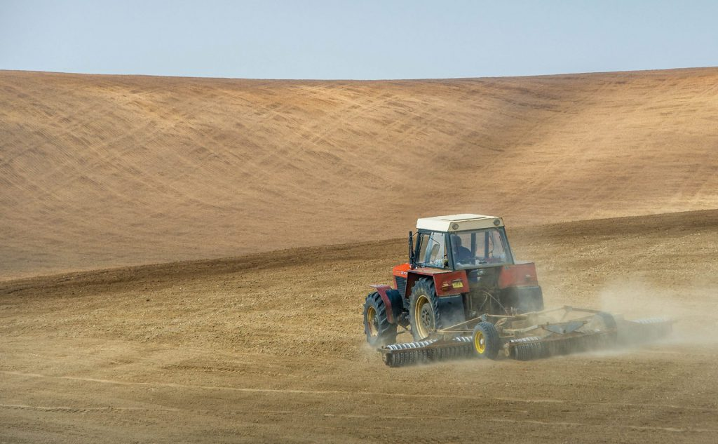 Landscape photo of a farmer working on his hilly fields in Moravia